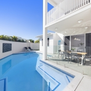 large pool beside a tall white two storey home