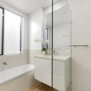 bathroom with bath and glass walled open plan shower