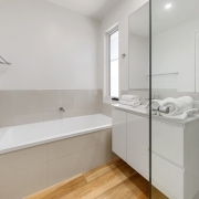 clean white bathroom with bath and white towels rolled up on the benchtop