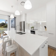 white modern kitchen with balcony in the background