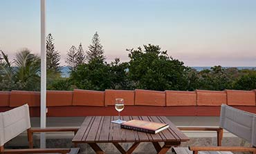 A glass of white wine and a book on an outdoor table with two chairs and an ocean view in the background