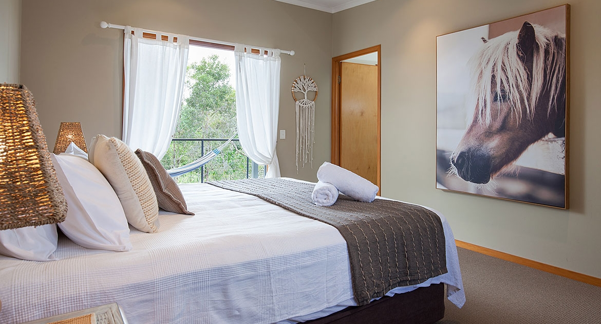 Queen bed room with large horse painting at Funky Beachfront House | Sunshine Coast Holiday Homes