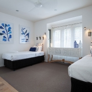 Single beds in a white room at Indigo Blue Beach House | Sunshine Coast Holiday Homes