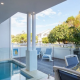 A clear blue water pool with glass fencing, outdoor chairs, table, terrace / patio and trees in the background.