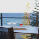 Two wines of bright red wine on a table facing the ocean