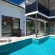 A modern pool with daybeds, glass fencing and an overlooking balcony