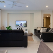 Living room with TV on | Beach Wave House