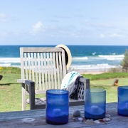 3 blue containers and a deck chair in front of ocean backdrop | Saltwater Beach House