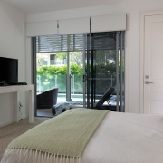 Bedroom on first flow that has direct access to outdoor deck at Whitehaven Beach House Coolum holiday homes.