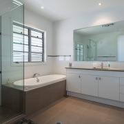 Bathroom with single sink and shower cubicle at Whitehaven Beach House Coolum holiday homes.