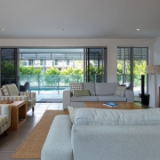 Wide angle shot of living room that flows out onto pool area at Whitehaven Beach House Coolum holiday homes.