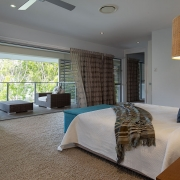 Bedroom that flows out onto balcony with wicker chairs at Whitehaven Beach House Coolum holiday homes.