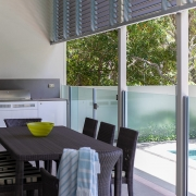 Outdoor BBQ area with enclosed pool at Whitehaven Beach House Coolum holiday homes.