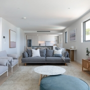 Living area with TV overlook kitchen at at Thalassa Beachfront Penthouse Coolum holiday homes.