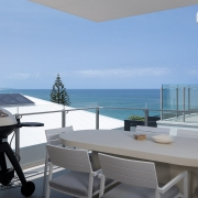 Outdoor BBQ terrace overlooking blue ocean with blue skies at Thalassa Beachfront Penthouse Coolum holiday homes.