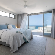 Bedroom that overflows onto outdoor terrace overlooking beautiful ocean view at Thalassa Beachfront Penthouse Coolum holiday homes.