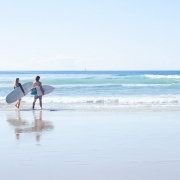 Male and female surfer with boards under their hands ready to catch a wave at Coolum Beach.