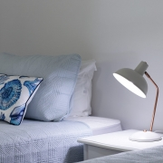Close up of single beds with a lamp on a side table at The Pool House Coolum Beach holiday home rentals.