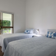 Bedroom with access to backyard with two single beds at The Pool House Coolum Beach holiday home rentals.