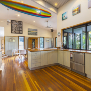 Kitchen side view with rainbow surfboard hanging up on the wall at Coolum Beach Bare Feet Retreat Holiday Home.