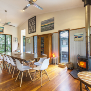 View of fireplace and main dining at Coolum Beach Bare Feet Retreat Holiday Home.