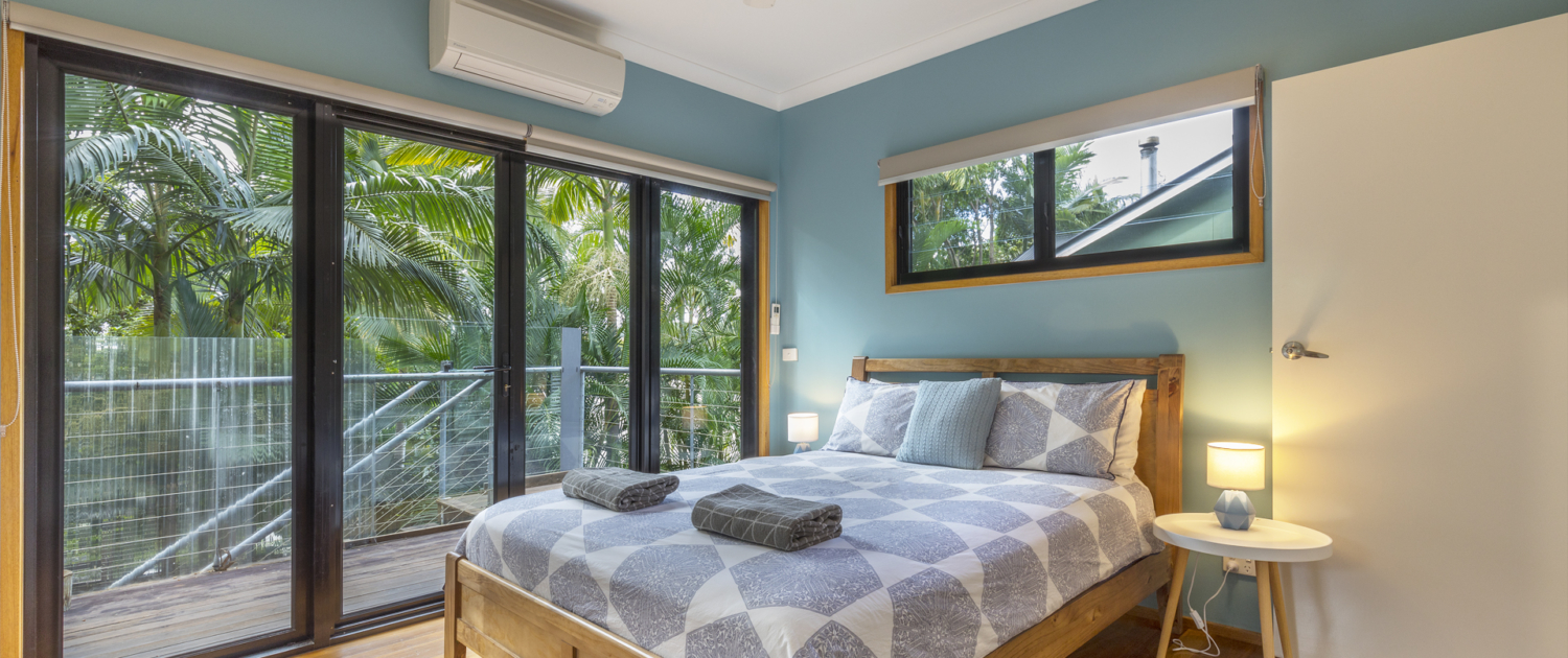 Master bedroom looking out at verandah and native palms at Coolum Beach Bare Feet Retreat Holiday Home.