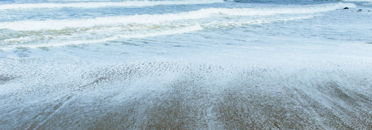 Multiple waves rolling onto shore and covering the edges of the sandy beach.