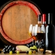Three bottles and glasses of wine surrounded by grapes and cheese in front of a wine barrel.